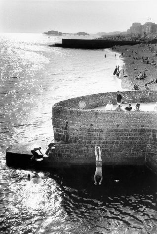 Diving from the Albion Groyne, c. 1980s: A group of people watch as a man dives into the sea from the Albion Groyne. The West Pier can be seen against the horizon. Photograph Copyright Evening Argus. | Image reproduced with kind permission from Brighton and Hove in Pictures by Brighton and Hove City Council
