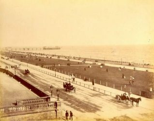Brunswick Lawns, c. 1905: Brunswick Lawns looking east from the entrance to Adelaide Crescent towards the West Pier. People are promenading along the lawns while horse-drawn carriages travel along Kingsway. | Image reproduced with kind permission from Brighton and Hove in Pictures by Brighton and Hove City Council