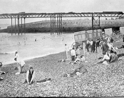 Men's Bathing Beach, 1895: Men and boys bathing at low tide, on the men's bathing beach, east of the skeleton Palace Pier which would open to the public in May 1899. | Image reproduced with kind permission from Brighton and Hove in Pictures by Brighton and Hove City Council