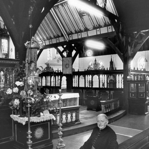 Interior of the Church of the Annunciation, c. 1970: The interior of the Church of the Annunciation with its vicar. This Anglican red-brick and flint Church was built for Revd Arthur Wagner to an Early English design by William Dancy and opened on 15 August 1864. In 1881 the aisles and the south chapel were added. The church was further extended in 1892 by F. T Cawthorn who also installed the east window with stained glass by Sir Edward Burne-Jones, which had previously been at St. Nicholas' Church since 1853. | Image reproduced with kind permission from Brighton and Hove in Pictures by Brighton and Hove City Council