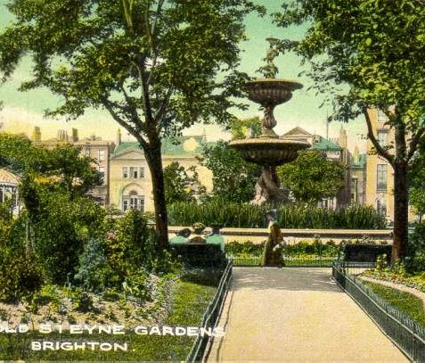 Old Steine Gardens , c. 1907: A coloured postcard of the Old Steine Gardens, centered on the Victoria Fountain which was unveiled on 25 May 1846 for Queen Victoria's 27th birthday. Designed by Amon Henry Wilds, it was cast at the Eagle Foundry in Gloucester Road. Three women are sitting on benches and one woman walks by. | Image reproduced with kind permission from Brighton and Hove in Pictures by Brighton and Hove City Council