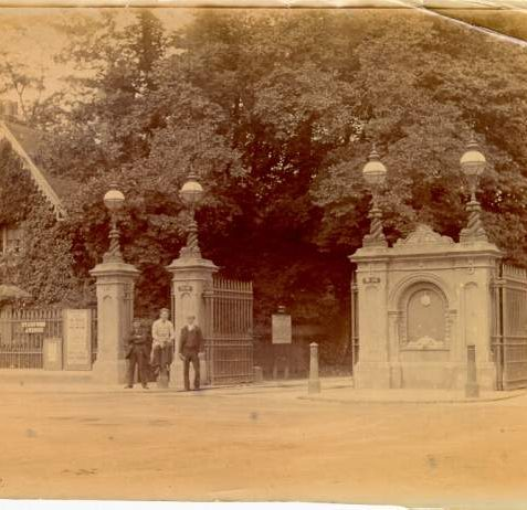 Preston Park , c. 1900:  Three men at the gates of Preston Park, at the south end of Stanford Avenue. The gate piers and cast-iron gates were designed by Philip Lockwood, Borough Surveyor in 1883-84; the ironwork is by James Longley of Crawley. To the left is the park superintendent's lodge. The gates and the lodge were demolished in 1928. | Image reproduced with kind permission from Brighton and Hove in Pictures by Brighton and Hove City Council