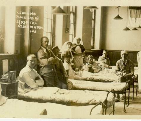 Wounded Soldiers in Hospital at Brighton, c. 1915: This photograph shows six soldiers, some in bed, and three nurses in a ward. During the 1914-18 war, military hospitals were set up in requisitioned buildings, including the recently completed Brighton, Hove and Sussex Grammar School, the Royal Pavilion and the Brighton Workhouse (now Brighton General Hospital) which became the Kitchener Military Hospital, where this photograph was taken. | Image reproduced with kind permission from Brighton and Hove in Pictures by Brighton and Hove City Council