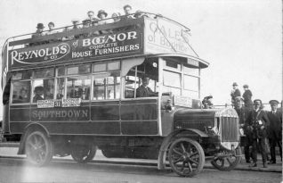 Southdown Open-top Omnibus, c. 1920: A Southdown open-top omnibus, running the 31 service from Brighton to Portsmouth via Worthing, Littlehampton, Bognor and Chichester. On the right a conductor can be seen with his characteristic leather bag and ticket-issuing machine. There are advertisements for Gales of Bognor and Reynolds and Co. house furnishers of Bognor. Southdown Motor Services Ltd was formed in 1915 and used Madeira Drive as a terminus until 1929 when Pool Valley bus station was created by Brighton Corporation. | Image reproduced with kind permission from Brighton and Hove in Pictures by Brighton and Hove City Council