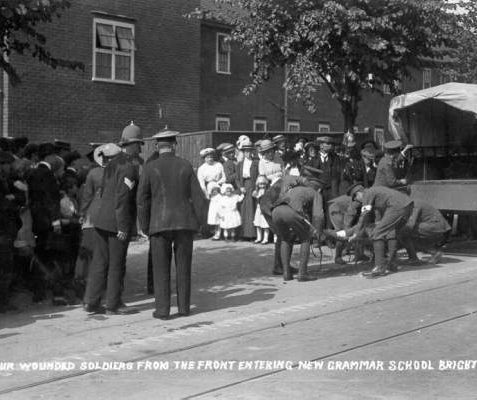 Arrival of Wounded Soldiers Entering New Grammar School, 1914: The Brighton, Hove and Sussex Grammar School building (now BHASVIC) on Dyke Road, was requisitioned for use as a military hospital soon after it was been in 1914. In this postcard Red Cross staff are unloading a wounded soldier on a stretcher from a canvas-sided truck, watched by a crowd of people and a policeman. | Image reproduced with kind permission from Brighton and Hove in Pictures by Brighton and Hove City Council