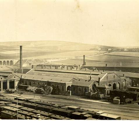 Engine Sheds at Brighton Station., 1868: Aerial view of trains and engine sheds at Brighton Station. The New England Hill viaduct can be seen on the left, a windmill to the right. Little development of Brighton has yet taken place in this photograph. | Image reproduced with kind permission from Brighton and Hove in Pictures by Brighton and Hove City Council