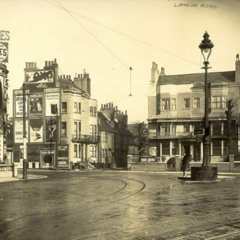London Road junction with North Road and Marlborough Place, c. 1930: A view of London Road at the junction with North Road and Marlborough Place, showing tram lines and overhead electrical cables. At the bottom of North Road a poster proclaims that