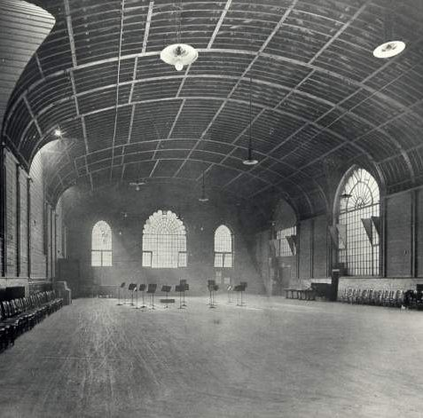 Interior of Corn Exchange , c. 1934: A group of music stands indicate that music practise may have been taking place. Alterations to the interior were made in 1934 by Robert Atkinson, including removal of the Royal Box and a construction of a new entrance in Church Street. The interior was restored to one large room with new windows in Church Street similar to the originals. | Image reproduced with kind permission from Brighton and Hove in Pictures by Brighton and Hove City Council