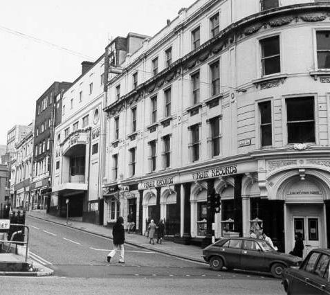 North Street and Queen's Road, 28 January 1974: This photograph shows an early Virgin Records shop at the western end of North Street. Nearby the Regent Cinema is closed awaiting demolition. Both of these buildings were demolished in 1974 and the site is now occupied by Boots the Chemists. A blue police box can be seen above the now filled-in public toilets under the clock tower | Image reproduced with kind permission from Brighton and Hove in Pictures by Brighton and Hove City Council