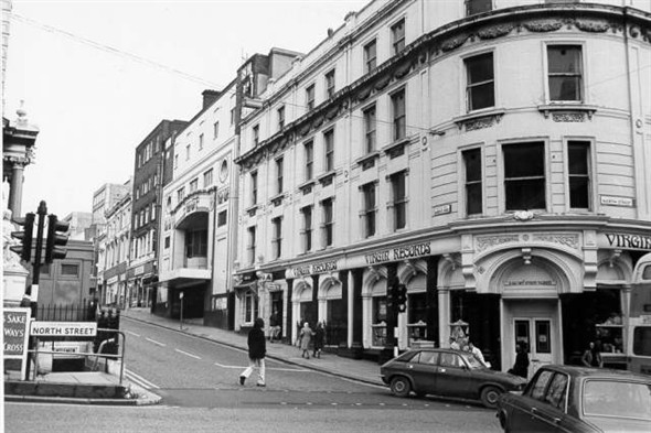 This photograph shows an early Virgin Records shop at the western end of North Street. Nearby the Regent Cinema is closed awaiting demolition. Both of these buildings were demolished in 1974 and the site is now occupied by Boots the Chemists. A blue police box can be seen above the now filled-in public toilets under the clock tower. | Royal Pavilion and Museums Brighton and Hove
