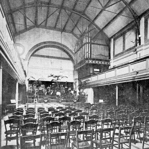 Concert Room at the Athenaeum Hall, c. 1911: The Athenaeum Recreation Hall stood at 148 North Street and was entered through a narrow passage. It opened in 1890 and was used by the Brighton School of Music from 1892 onwards. The concert room pictured here could seat 500 people. Later used as a billiard hall and the Central Spiritualist Church, the hall was demolished in 1962 for the erection of Prudential House and road widening. | Image reproduced with kind permission from Brighton and Hove in Pictures by Brighton and Hove City Council