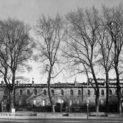 Percy and Wagner Almshouses, c. 1970: In 1795 six yellow-brick almshouses were built in memory of the late Dorothy and Philadelphia Percy, daughters of the Duke of Northumberland. They housed six poor widows of the Church of England, who were also granted £48 a year and a new gown and cloak every two years. These, now numbers 4 to 9, were the first Gothic revival buildings in Brighton. In 1859 more almshouses were added either side by Revd Henry Wagner and his sister Mary, in memory of the Marquess of Bristol. In the 1960s there were plans to demolish these almshouses, but in March 1971 they were listed and restored in 1975-6. | Image reproduced with kind permission from Brighton and Hove in Pictures by Brighton and Hove City Council