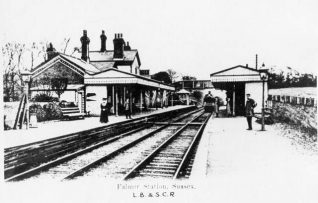 Falmer Station, c. 1905: People waiting on the platforms of Falmer Station as a train approaches the station. At this time the station was part of the London, Brighton and South Coast Railway. Falmer Station opened on 8 June 1846 on the eastern side of the village when the railway line opened, and reopened on 1 August 1865 at the current site. In 1890 the station was rebuilt with an integrated station-master's house within the building.   Image reproduced with kind permission from Brighton and Hove in Pictures by Brighton and Hove City Council