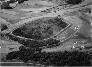 Hill Fort at Hollingbury Camp, 1954. An aerial view of Hollingbury Camp, showing features of the Iron Age hill fort and of the surrounding landscape. Dating from the sixth century to about the middle of the second century BCE, it is a scheduled ancient monument, covering about 9 acres in a rough square about 600 feet across, with gateways to east and west through ramparts that can still be seen. The camp was excavated in 1908 by Herbert S. Toms, a Curator at Brighton Museum, by Cecil Curwen and Brighton and Hove Archaeological Society in 1931, and by John Holmes in 1967. The sites of some wooden huts have been discovered within the fort. | Image reproduced with kind permission from Brighton and Hove in Pictures by Brighton and Hove City Council